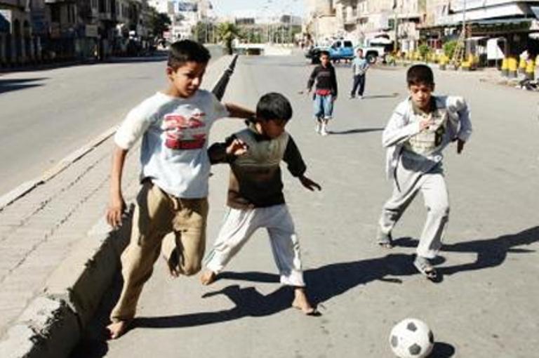 صورة اطفال يلعبون كرة القدم في الطريق